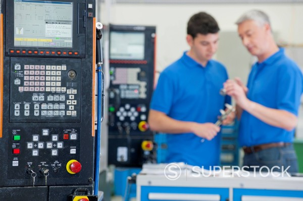 Stock Photo: 4208R-31985 Engineers discussing machine parts in manufacturing plant