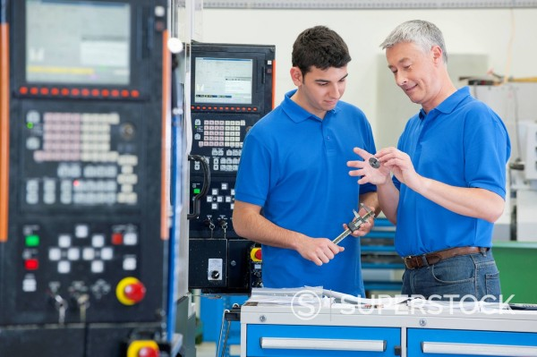 Engineers discussing machine parts in manufacturing plant : Stock Photo