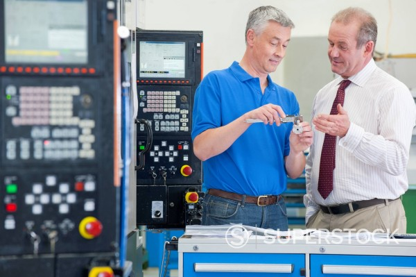 Stock Photo: 4208R-31987 Businessman and engineer discussing machine parts in manufacturing plant