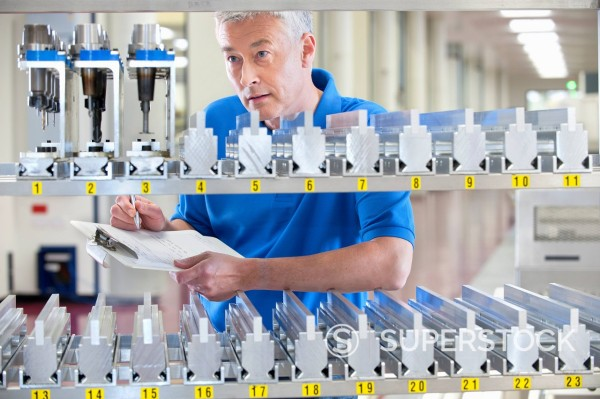 Technician checking inventory of machine parts in manufacturing plant : Stock Photo