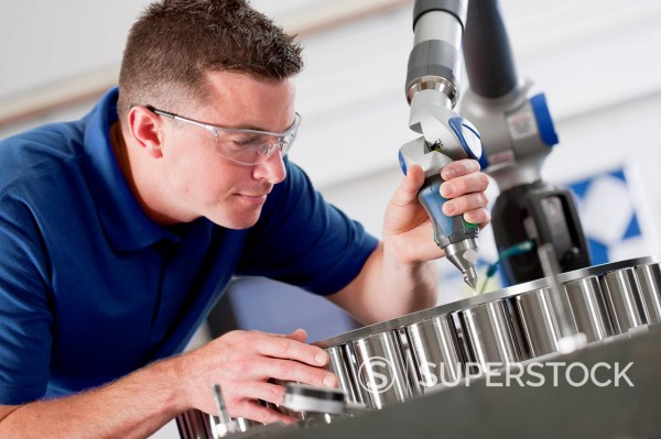 Technician using measurement probe on assembly line in steel bearing manufacturing plant : Stock Photo