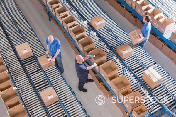 Stock Photo: 4208R-32071 Workers packing boxes on conveyor belts in distribution warehouse
