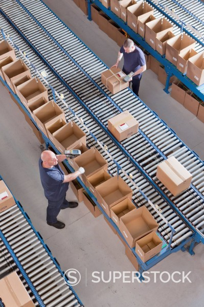 Stock Photo: 4208R-32081 Workers packing boxes on conveyor belts in distribution warehouse