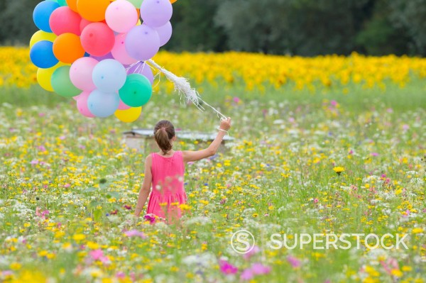Girl carrying bunch of balloons among wildflowers in sunny meadow : Stock Photo