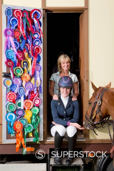 Stock Photo: 4208R-32287 Portrait of smiling mother and daughter in equestrian uniform with horse in doorway of trailer with rosettes covering door