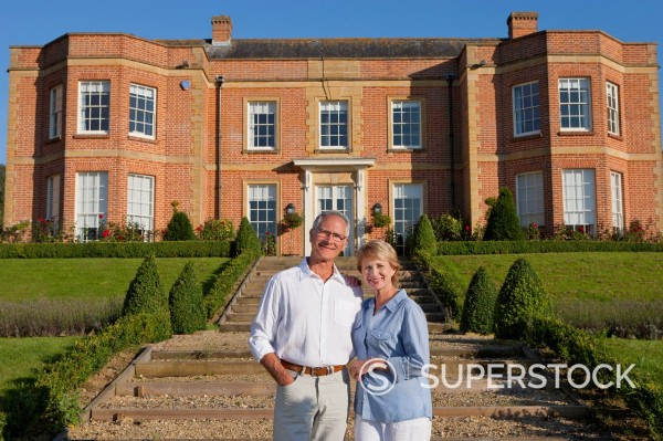 Stock Photo: 4208R-32619 Portrait of smiling couple in front of luxury estate