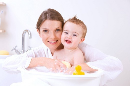 Mother giving baby a bath : Stock Photo