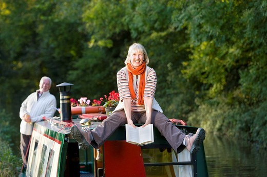 Stock Photo: 4208R-3488 Happy woman holding book on narrow boat in canal