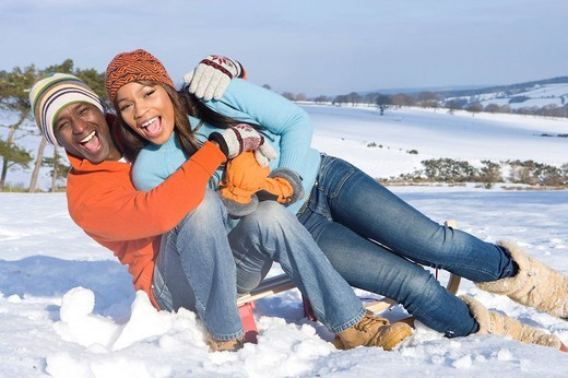 Playful couple sitting in snowy field : Stock Photo