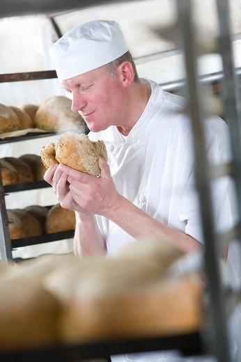 Baker smelling fresh bread from oven : Stock Photo