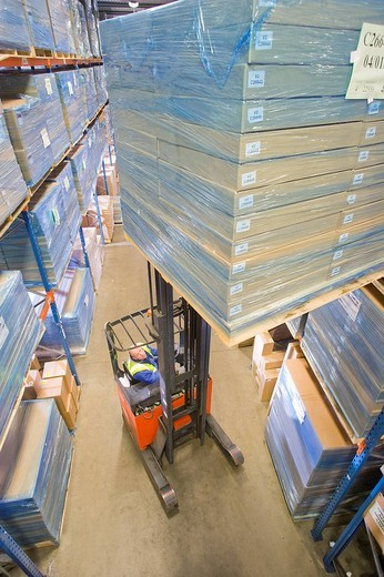 Warehouse worker moving boxes on forklift : Stock Photo