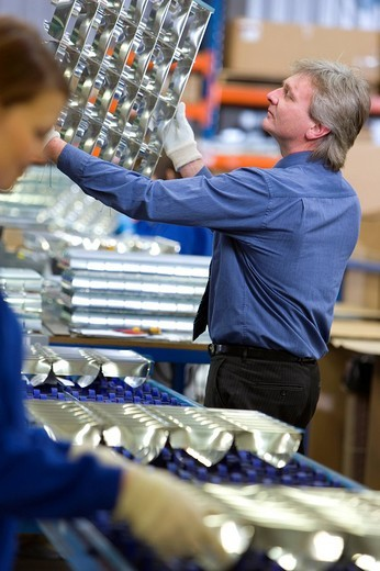 Manager inspecting trays of aluminium light fittings in factory : Stock Photo