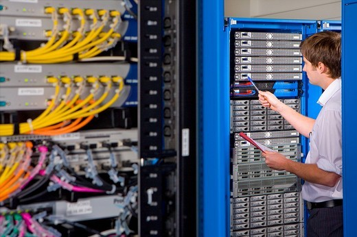 IT technician with folder checking network server : Stock Photo