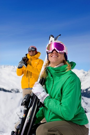 Happy couple wearing goggles and holding skis on snowy mountain : Stock Photo