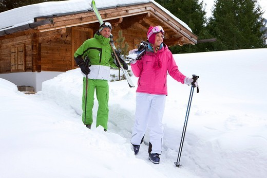 Couple standing in snow near lodge with skis : Stock Photo