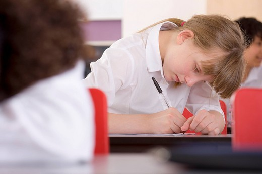 Stock Photo: 4208R-3838 School girl taking test on desk in classroom