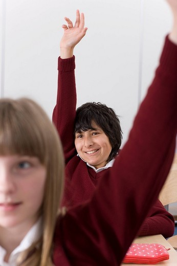 Students answering teacherÆs questions in classroom : Stock Photo