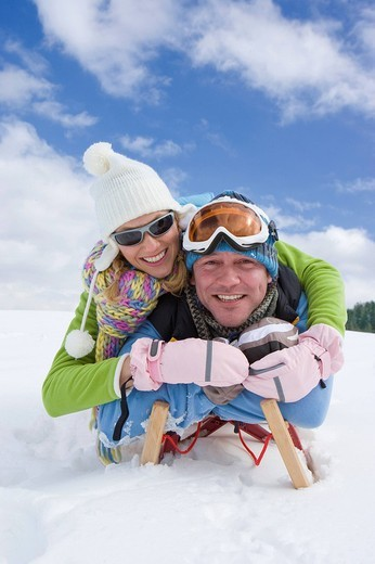 Stock Photo: 4208R-3947 Couple laying on sled in snow together