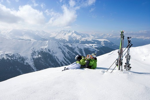 Couple laying in snow on mountain top with skis : Stock Photo