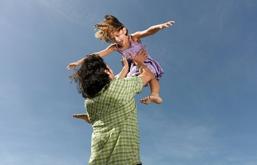 Stock Photo: 4208R-4017 A father throwing his daughter in the air