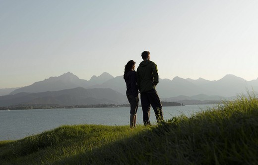 A couple looking out across a lake at sunset : Stock Photo