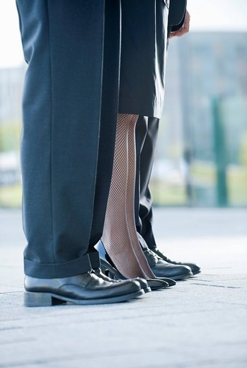 Two businessmen and a businesswoman standing in a row, close_up of their legs : Stock Photo