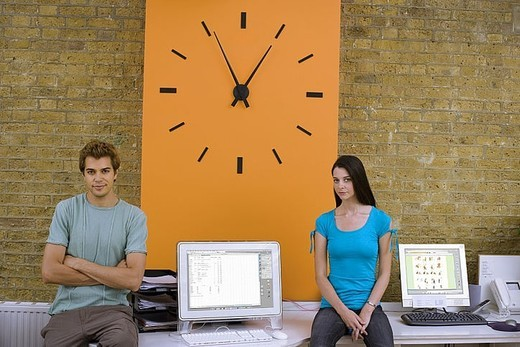 Stock Photo: 4208R-4045 Young man and woman sitting on desk in office next to large orange wall clock, smiling, portrait