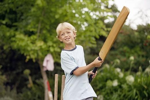 Blonde boy 8-10 playing cricket in garden, swinging bat, smiling : Stock Photo