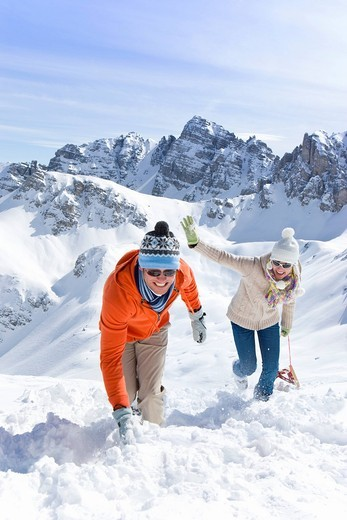 Stock Photo: 4208R-4212 Smiling couple with sled climbing hill with mountain in background
