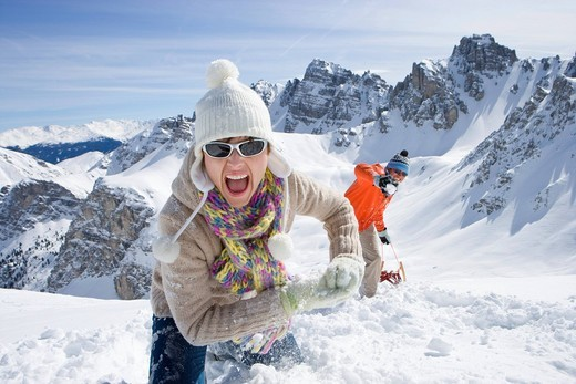 Stock Photo: 4208R-4215 Smiling couple with sled climbing hill with mountain in background