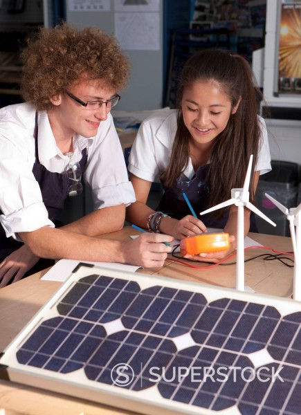 Students learning about wind power and solar panels in vocational school : Stock Photo