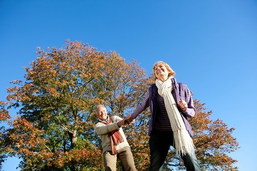 Stock Photo: 4208R-4390 Happy senior man walking and holding hands with wife in autumn