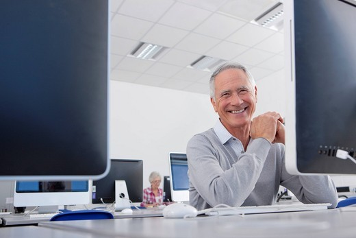 Smiling adult student studying in college evening class computer lab : Stock Photo
