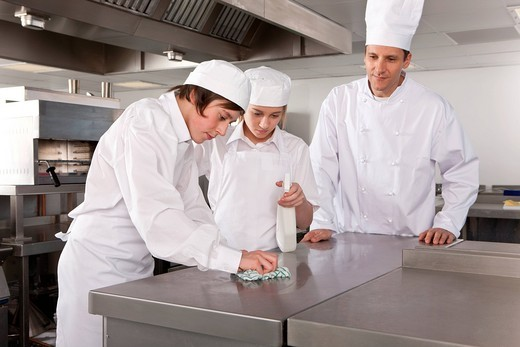 Chef watching trainees cleaning work surface in commercial kitchen : Stock Photo
