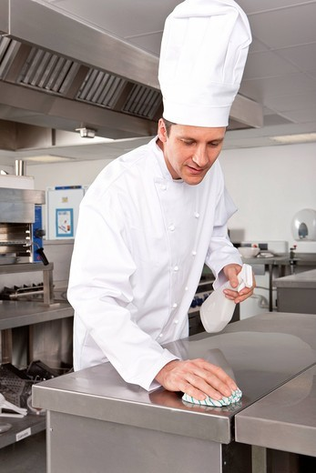 Stock Photo: 4208R-4521 Chef cleaning work surface in commercial kitchen