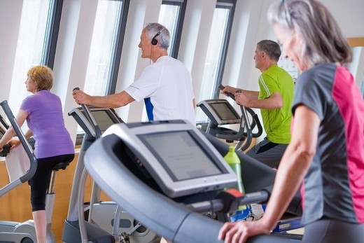 Stock Photo: 4208R-4693 Seniors exercising on cross training machines in gym