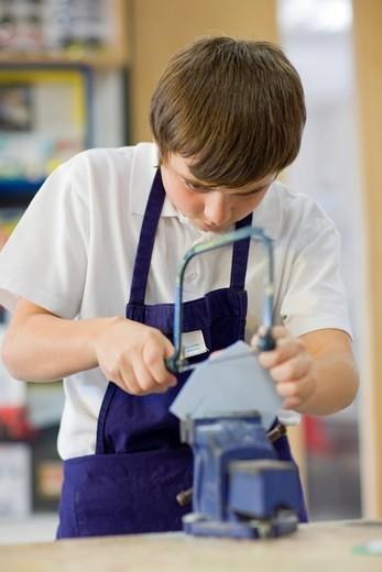 Boy using saw in school workshop : Stock Photo