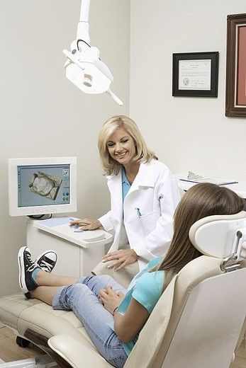Stock Photo: 4208R-4850 Female dentist talking to patient sitting in dentist´s chair in dental surgery, smiling