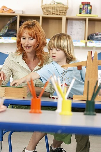 Boy 4-6 and teacher playing with weight scale on desk in classroom, smiling differential focus : Stock Photo
