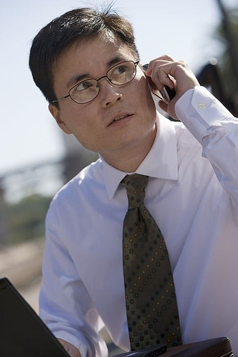Businessman in spectacles using laptop and mobile phone, outdoors, side view tilt : Stock Photo