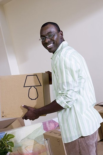 Man moving house, holding cardboard box in living room, smiling, side view, portrait tilt : Stock Photo