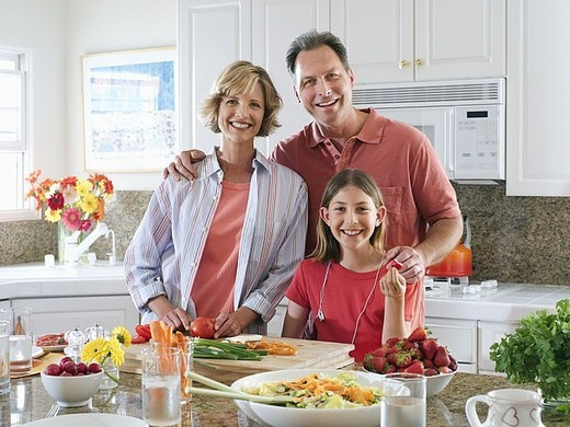 Family standing beside kitchen worktop, woman chopping tomatoes, smiling, front view, portrait : Stock Photo