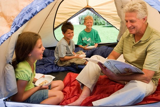 Family sitting inside tent on garden lawn, children 8-10 eating breakfast, grandfather reading magazine, smiling : Stock Photo