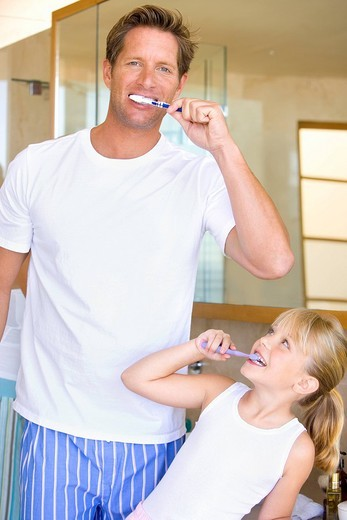 Father and daughter 6-8 brushing their teeth in bathroom, smiling : Stock Photo