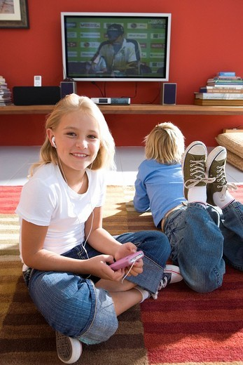 Boy and girl 6-8 on rug in front of television, portrait of girl smiling and using mp3 player : Stock Photo