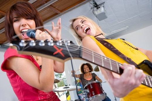 Three teenagers 15-17 in garage band, teenage girls singing and playing guitar in foreground : Stock Photo
