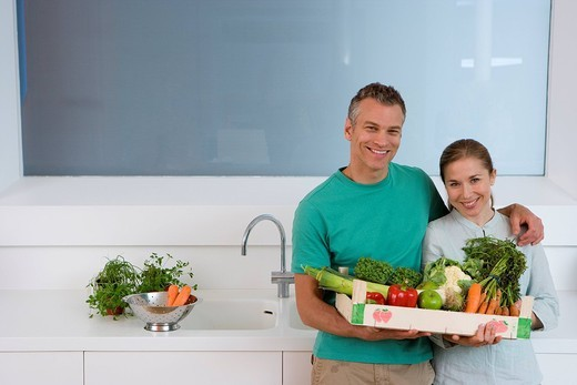 Couple in kitchen holding box of vegetables, smiling, portrait, elevated view : Stock Photo
