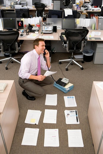 Businessman by piles of paperwork on floor, using telephone, smiling, elevated view : Stock Photo
