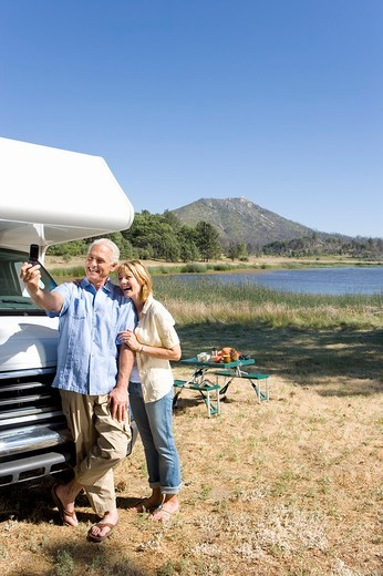 Stock Photo: 4208R-6103 Mature couple by lake and motor home taking photograph of themselves with mobile phone