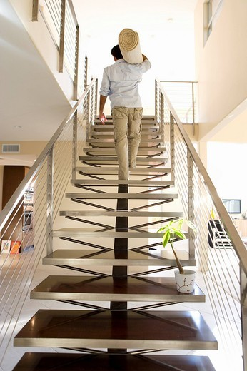 Stock Photo: 4208R-6409 Man carrying rolled carpet up stairs in new home